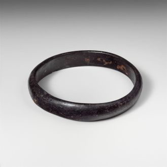 Glass bracelet, ca. 2nd–4th century A.D. Translucent dark blue, appearing black. Slightly oval band with uneven sides; semicircular in section with flat inner side; no visible seam. From Cyprus, said to be from a tomb at Idalion (modern Dali).