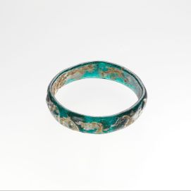 Glass bracelet with impressed decorationlate 4th–5th century A.D. from Cyprus Translucent turquoise blue. Circular band with rounded edges and slightly uneven sides; convex in section with flat inner side; no visible seam. Outer surface decorated with a series of thirteen stamped circles, each depicting a lion facing right with open mouth, large mane, and tail raised above his back. Around the outside of the bracelet is a pattern of stamped medallions containing lions.
