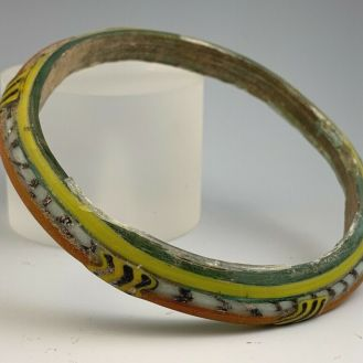 circa 1st-2nd Century A.D. multi-colored green glass bracelet. A green glass main bracelet with an orange, black, white and yellow trim decoration.  2.77 inches internal diameter; 3.37 inches external diameter.