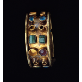Roman Empire, about A.D. 379–395, Gold, glass, and emeralds, 3.2 × 6.4 cm A heavy gold band elaborated by colored stones and glass forms this massive gold bracelet. The bracelet was made in two pieces, which were then hinged and secured with a pin decorated with green glass. The edges of the gold band are folded outwards at a perpendicular angle, forming a ledge that served to protect the stones. Blue, green, and red glass; emeralds; and now-missing pearls were placed in pairs in simple gold settings around the bracelet. The contrasting colors anticipated the EarlyByzantine interest inpolychromy. The bracelet was unusually heavy and probably was not very comfortable to wear. The shape of the bracelet is Roman, yet there is something distinctly non-Roman about it. It resembles jewelry made on the edges of theRoman Empire, which merged Roman and native tastes.