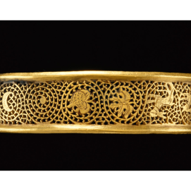 about A.D. 379–395, Gold, 1.4 × 6.3 cm Bracelet with Openwork (Display Title)A simple gold band with plain flanged edges forms this openwork bracelet. A vegetal scroll weaves across the surface of the band, into which hunting scenes are inserted. On one side a hound chases a stag, while on the other a hound pursues a hare. Vegetal scrolls enlivened with figures among the leaves and vines began inHellenistic art and remained popular throughout Roman art. The theme of the hunt was also a favorite subject in Late Roman art, taking on a larger, metaphorical meaning of victory in combat. Here, however, the hunt scenes include animals only and not the hunter.